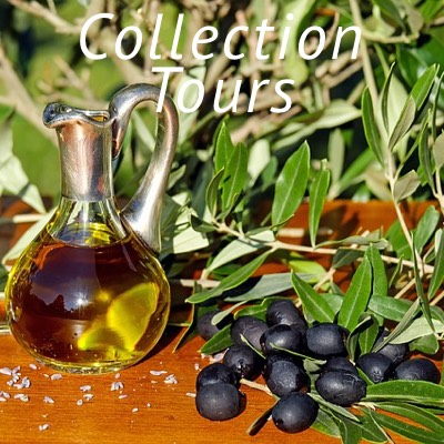 Carafe Filled with Greek Extra Virgin Olive Oil on a Table with Black Olives and Olive Branches